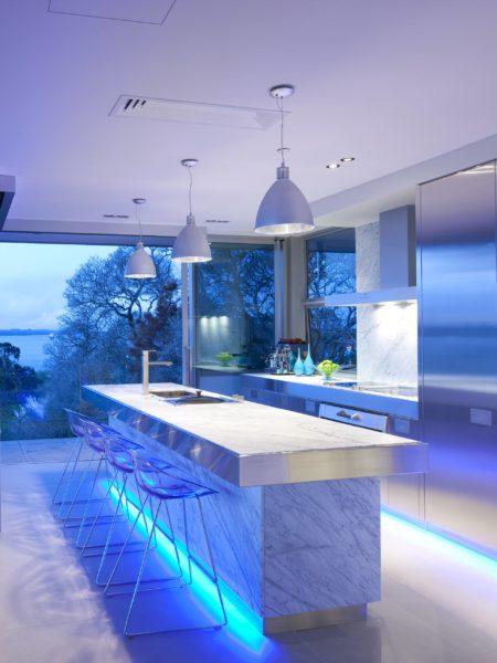 Необычная подсветка и яркое освещение переносят акцент кухни на остров.