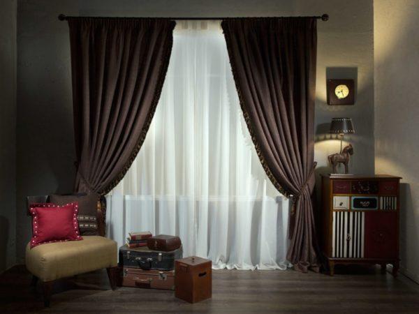 Темные шторы приглушают свет из окна, подчеркивая элегантные темные тона в интерьере комнаты.
