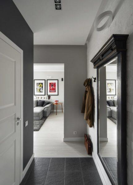 Прихожая в разных оттенках серого. Большое зеркало добавляет света помещению.