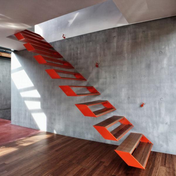 Степени попарно крепятся к стене, общая конструкция такой лестницы выглядит парящей и невесомой.