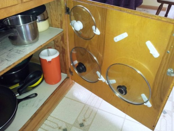 Хранение крышек на внутренней стороне шкафчика.