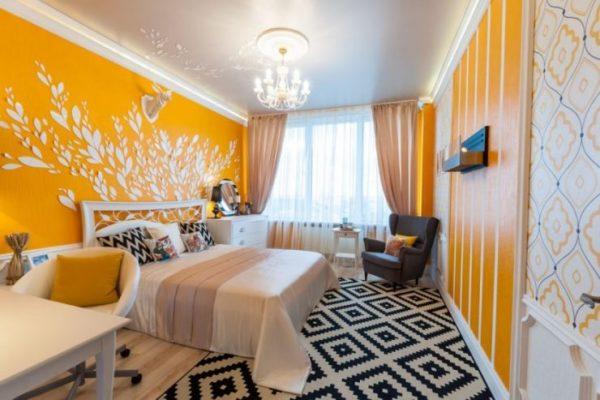 Спальня с яркими стенами, дополненными текстилем того же цвета, но более бледного оттенка.