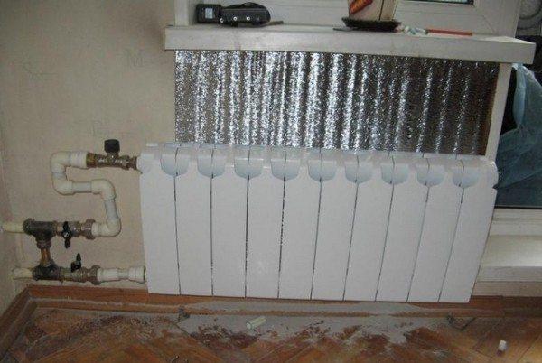 Фото фольгированного теплоизоляционного слоя за отопительным прибором